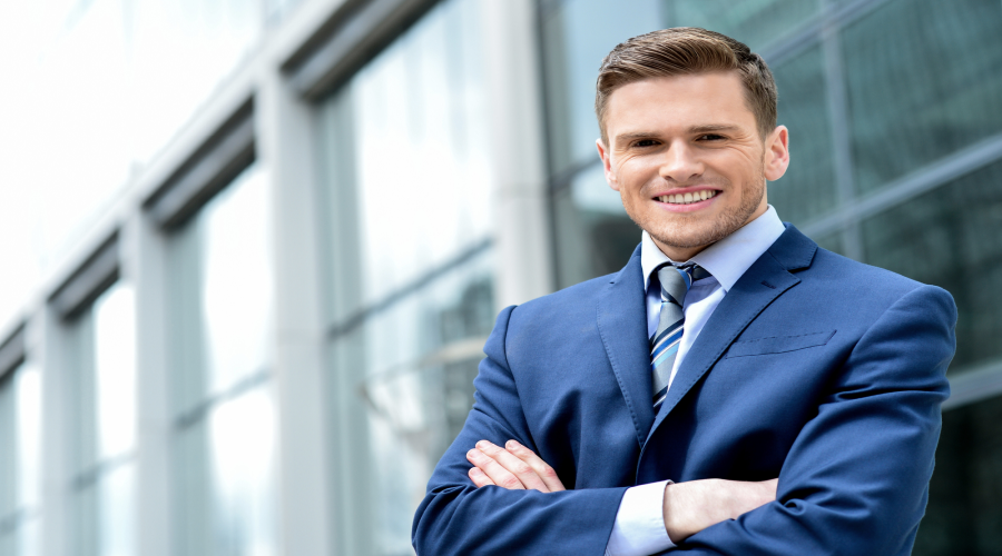13225664_young-businessman-smiling-in-a-office-outdoor 900x500